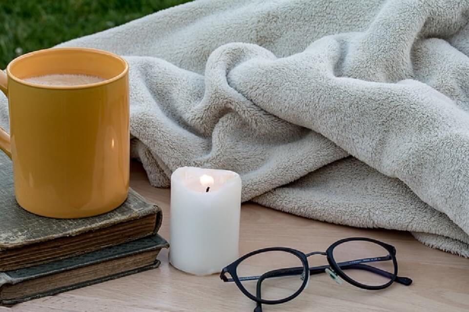 毛布とキャンドルのそばにあるコーヒーカップ
